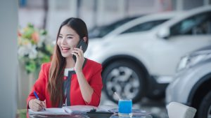 finding the right phone system for car dealerships woman on cell phone in front of cars